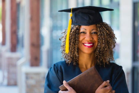 a woman holding her diploma to her chest smiling happy