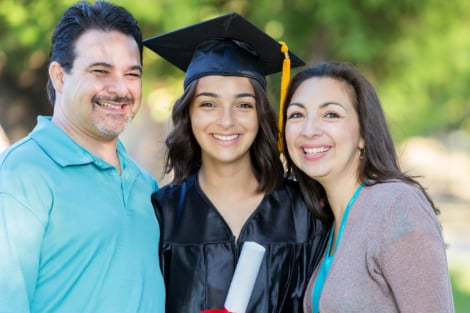 family smiling together with their recent graduate