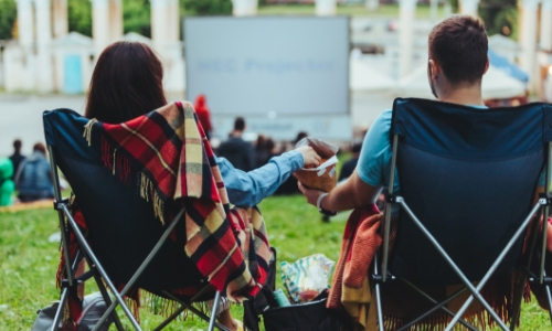 A couple sitting in camp chairs on a lawn watching a movie
