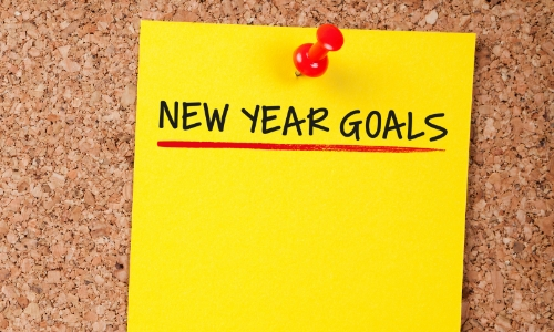 """New Year Goals"" written on a bright yellow sticky note"