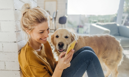 A woman smiling at her cell phone and petting her dog