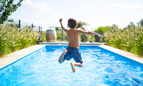 Young child jumps into private pool on a vacation.